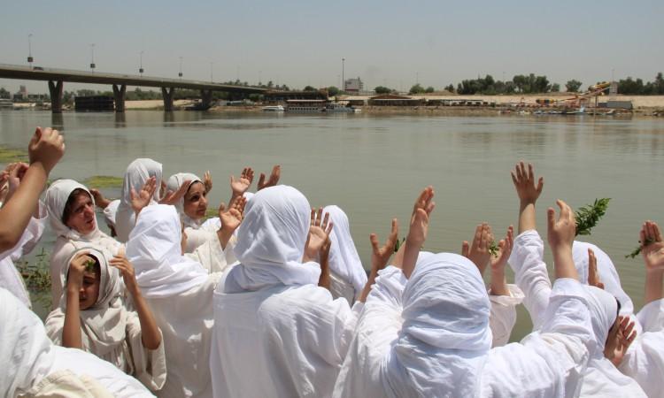 مندائيون بملابسهم البيضاء يتعمّدون في نهر دجلة (العراق). © Uday Khamas