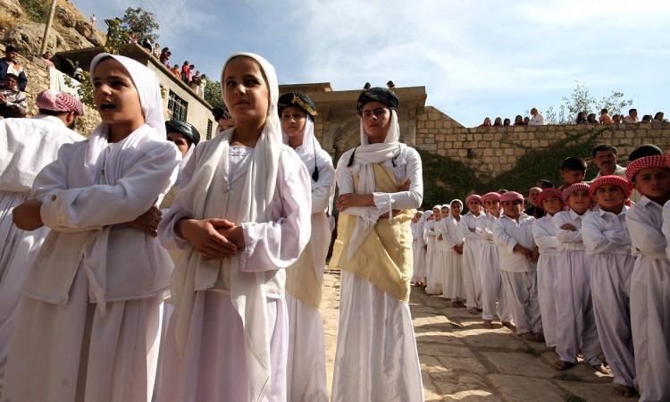 صبيان وبنات أيزيديّون ينشدون أغانٍ دينيّة في معبد لالش (العراق). - AFP ©